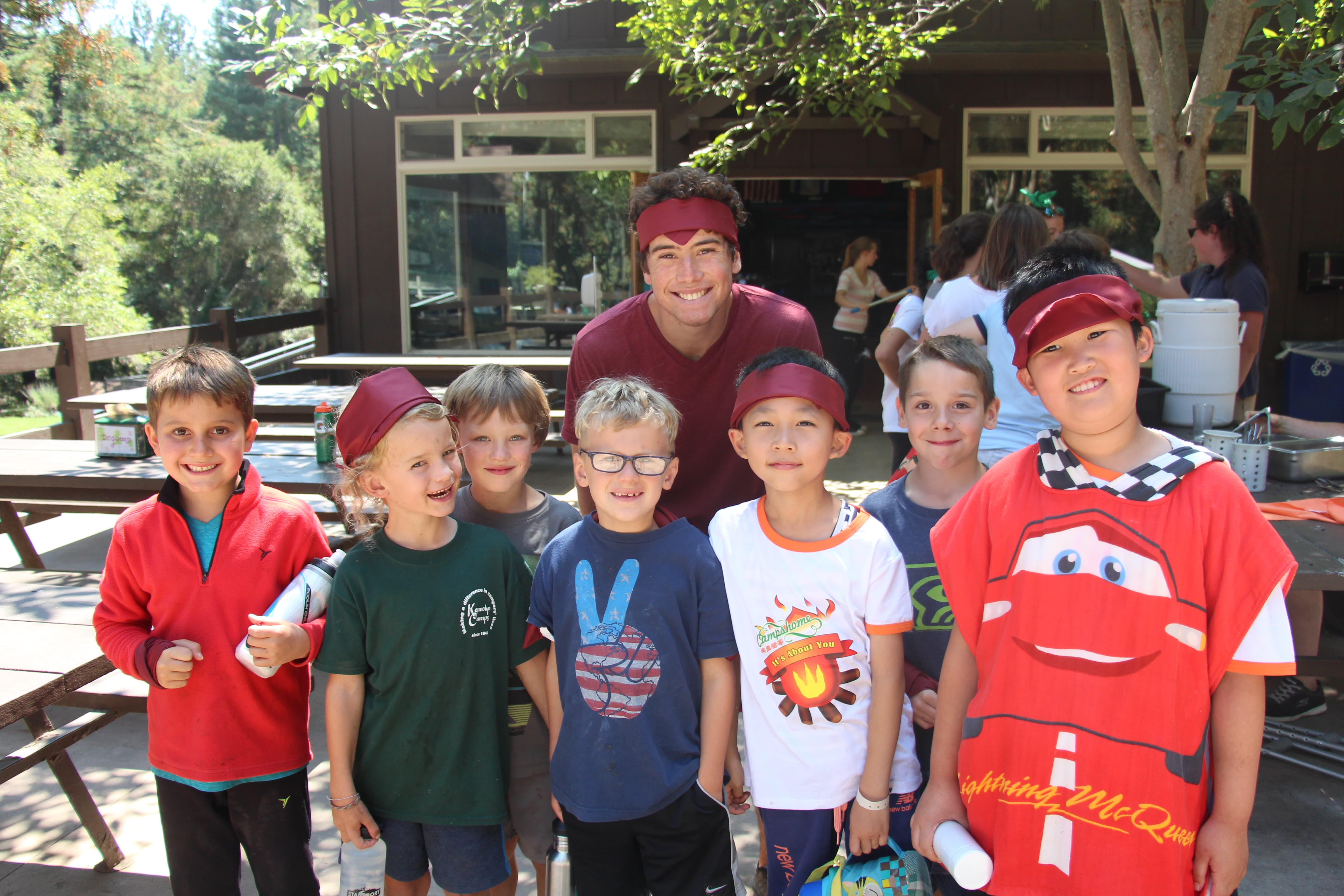 A counselor with a group of campers wearing maroon bandanas