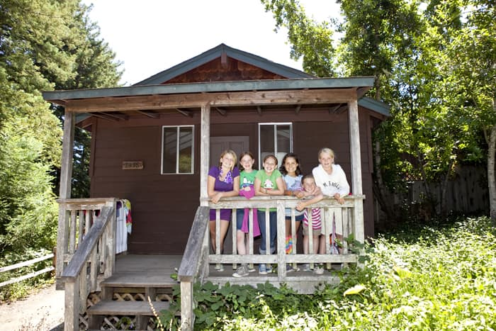 Six girls in front of a cabin smiling