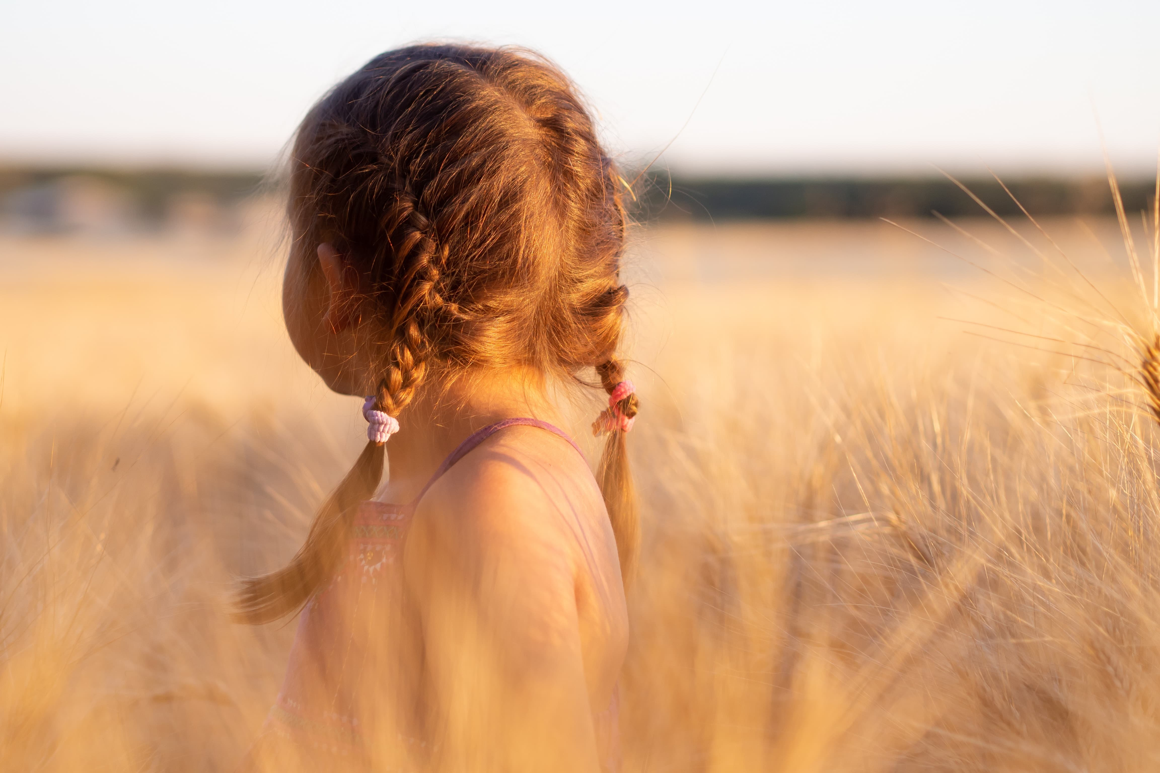 A girl in a field looking for something