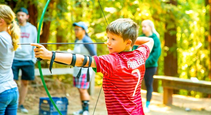 A camper aiming a bow and arrow