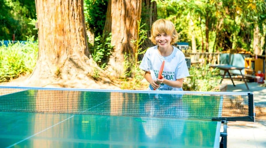 Boy plays ping pong at summer camp