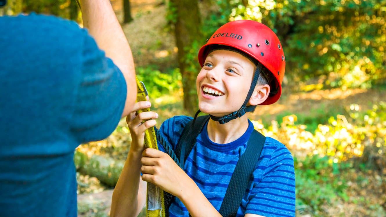 Smiling boy wearing red helmet at summer camp