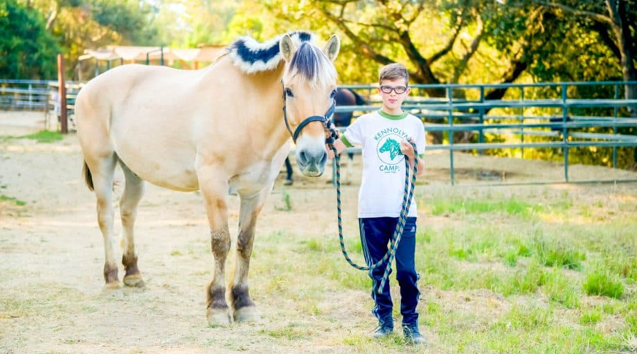 Boy walks pony at summer camp