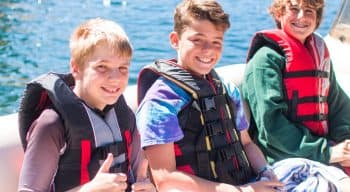 Three boys with life vests on a boat smiling