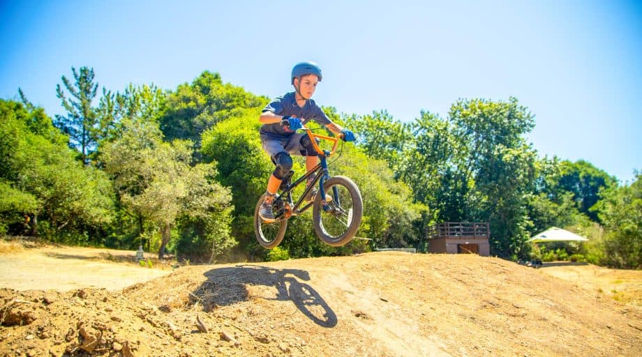 Boy jumps BMX bike at summer camp