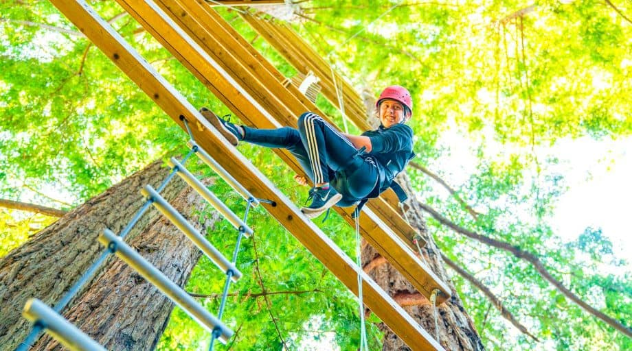 Camper climbs planks of ropes course