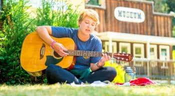 camper plays guitar while sitting on grass
