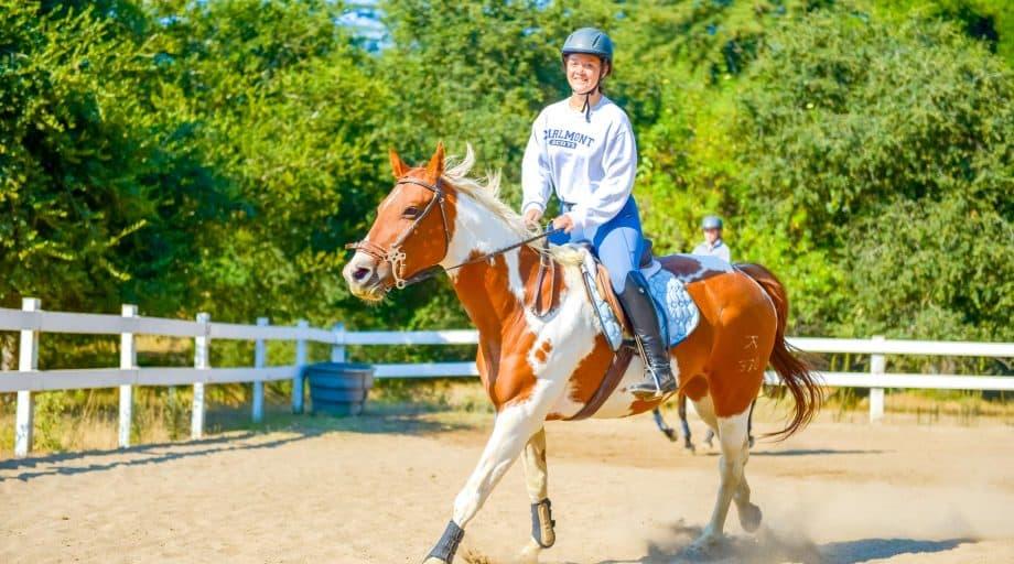Camper trots a horse at summer camp