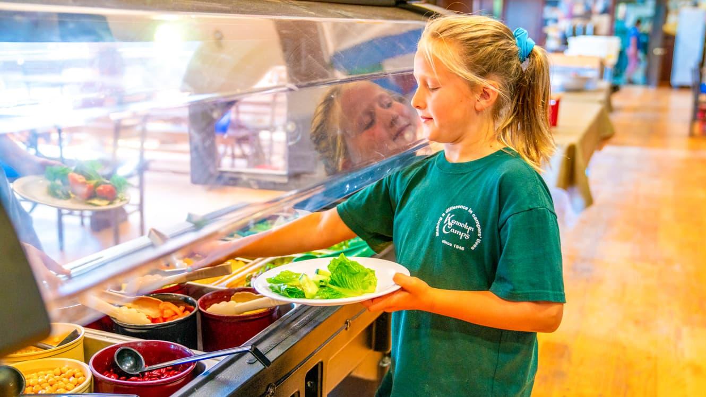 Girl gets lettuce from summer camp salad bar