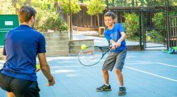 Summer camper practices tennis swing