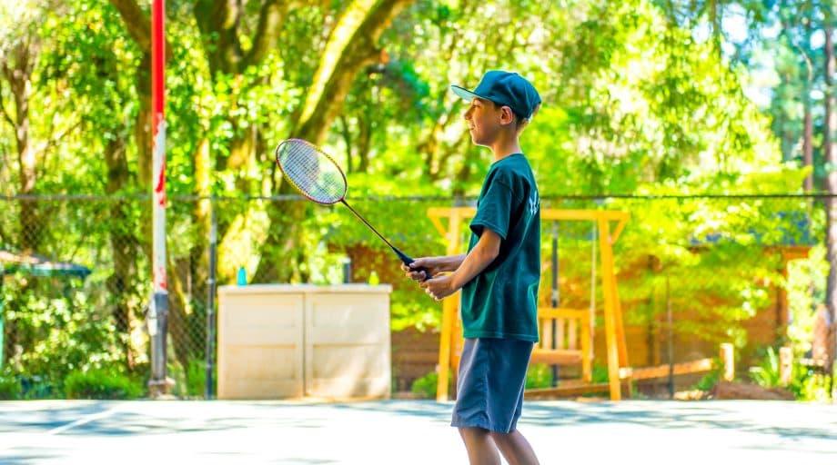 Camper holds tennis racquet