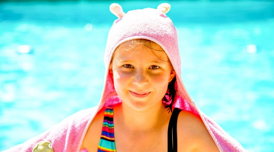 Camper sits by pool with pink towel over head