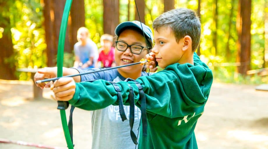 Two campers aim bow at summer camp