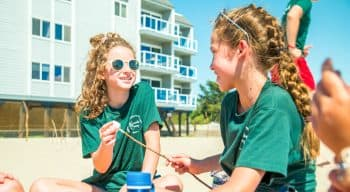 A girl with sunglasses talks to another girl with marshmallows on a stick