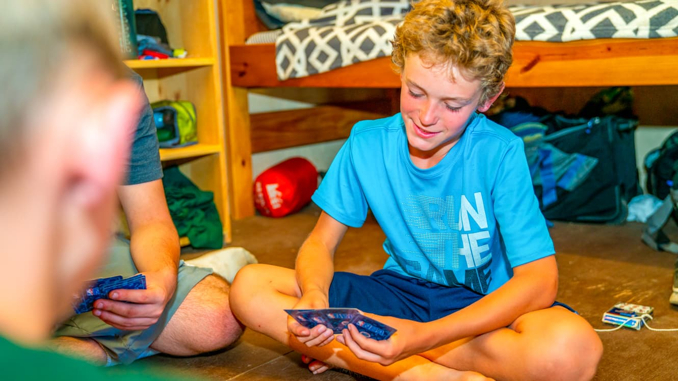 Boys play trading card game in camp cabin