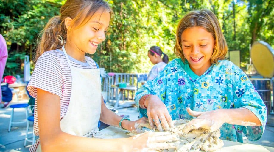 Two girls work with wet clay at summer camp