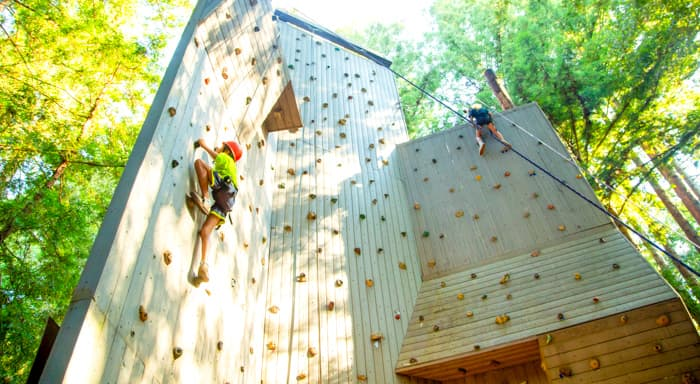 Two campers climbing a rock wall