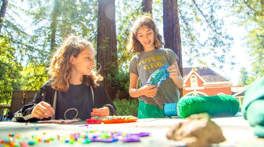 Girls do arts and crafts at summer camp
