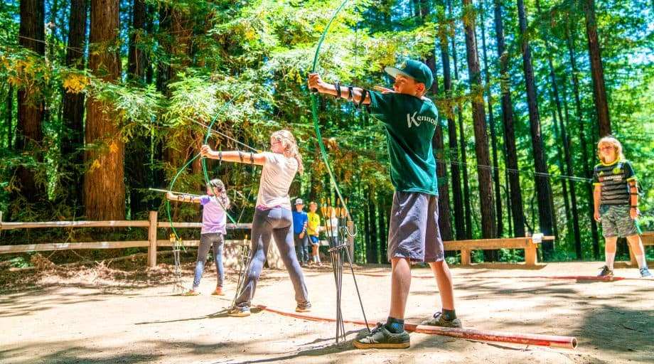Campers draw bows during archery