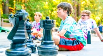 Campers listening to someone before playing giant chess