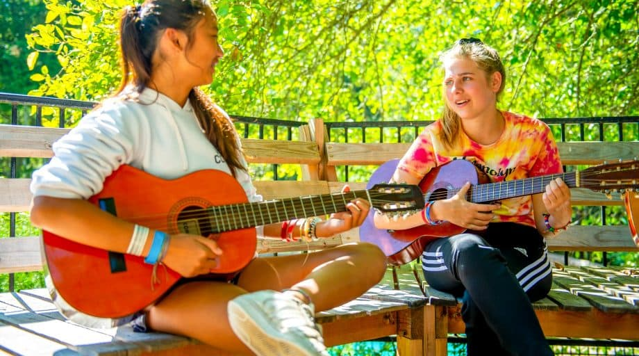Two girls play guitars at summer camp