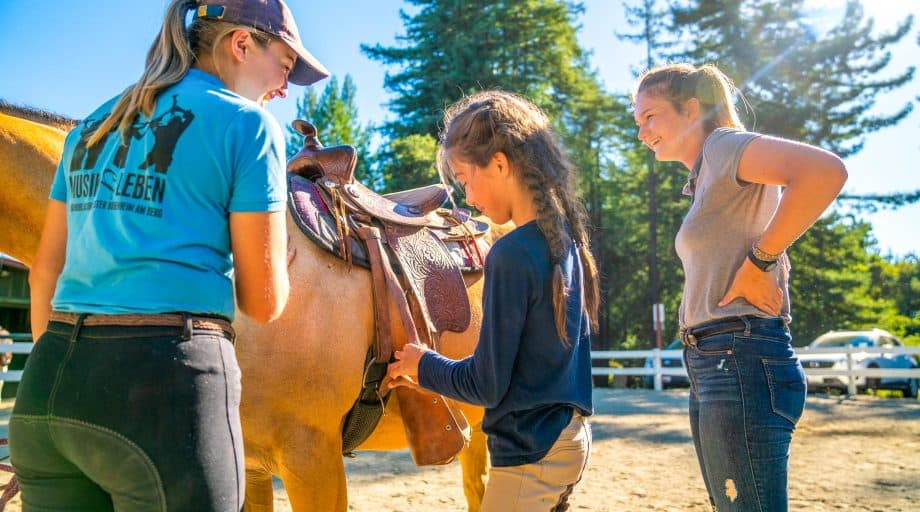 Camper and counselors tend to horse's saddle