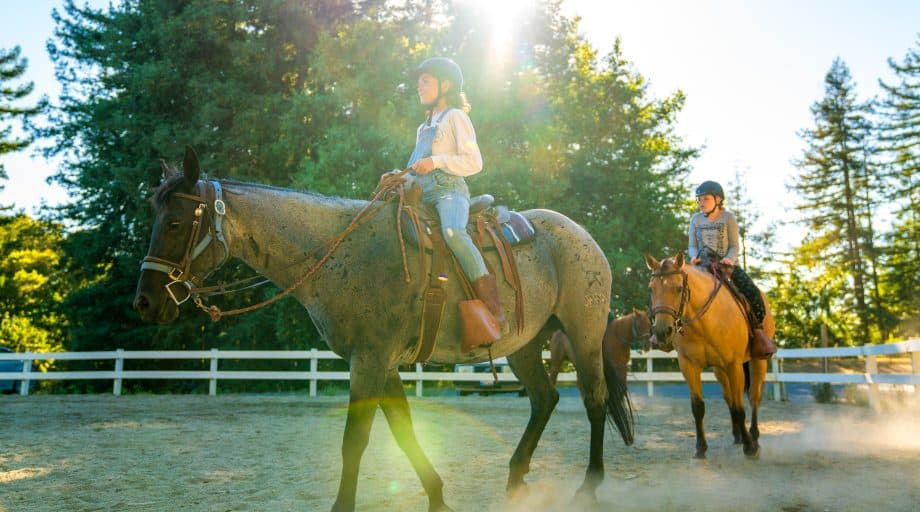 Campers ride horse in summer camp ring