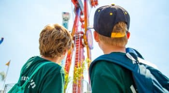 Two campers looking at a large amusement park ride
