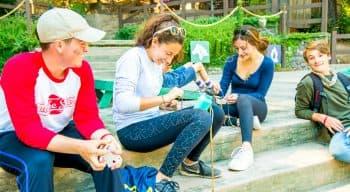 Campers making friendship bracelets outside for friends