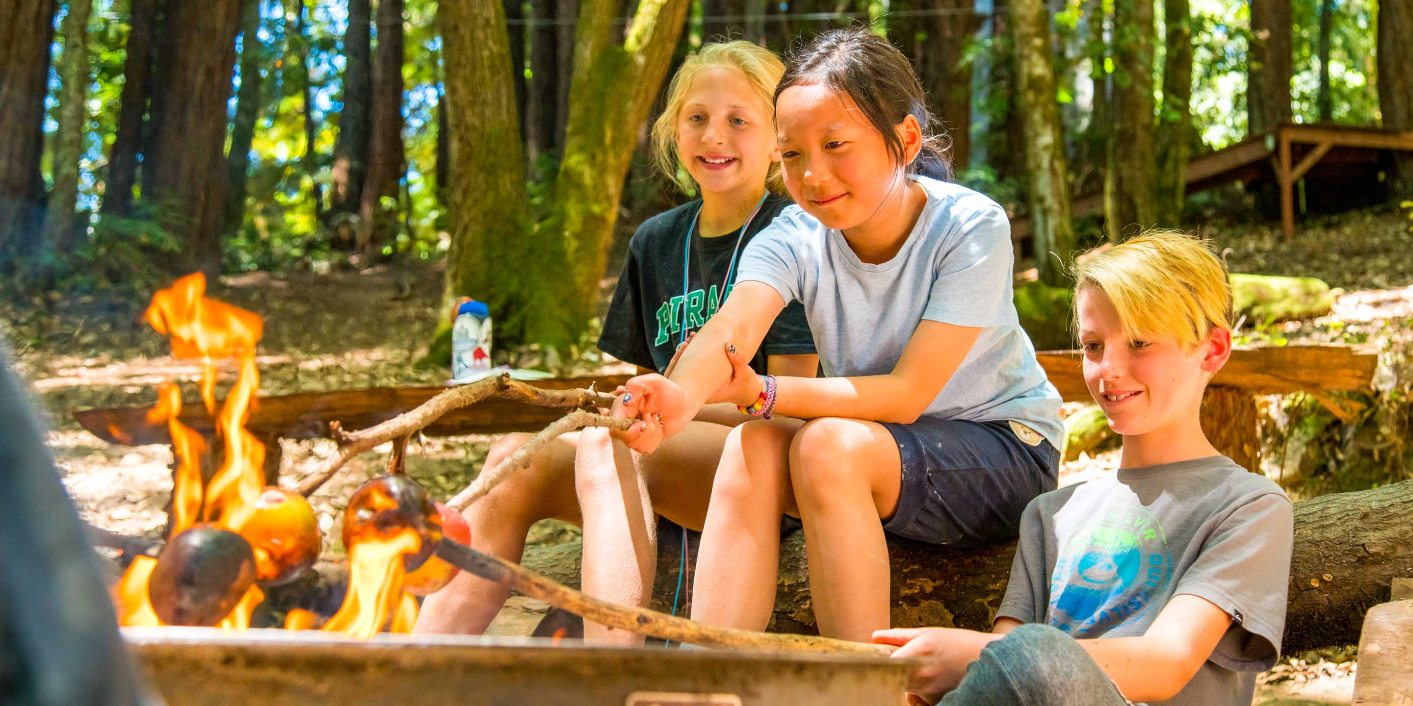 Campers roast apples over outdoor fire
