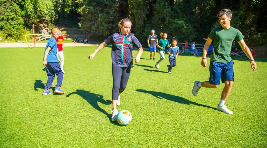 Group of campers play soccer at summer camp