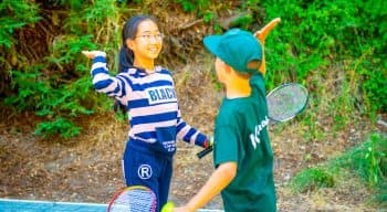 Campers high five on tennis court