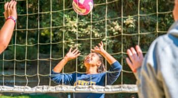 Girl prepares to hit volleyball at summer camp