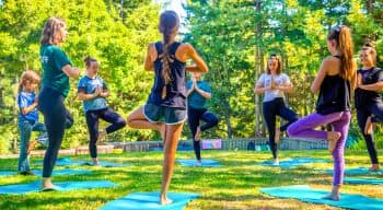 Campers outdoors in a circle doing yoga