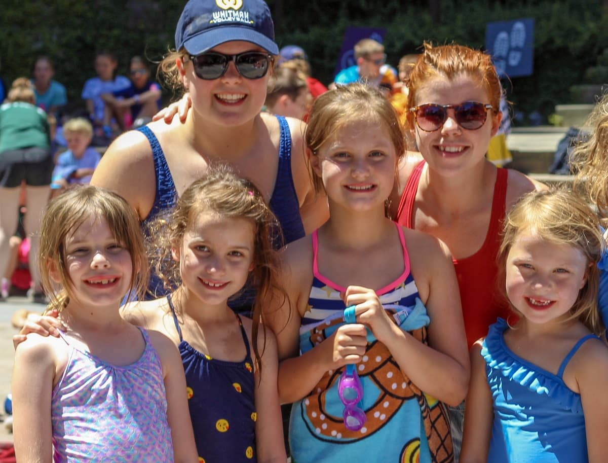 Counselors with campers smiling at the pool