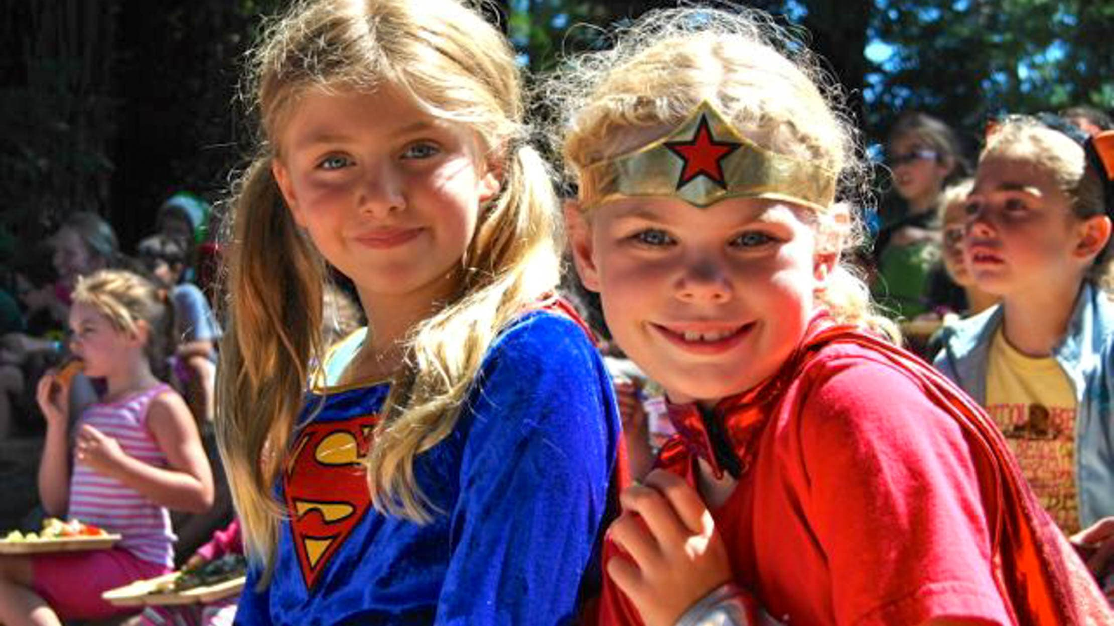 Girls dressed as Supergirl and Wonder Woman for Friday Funday