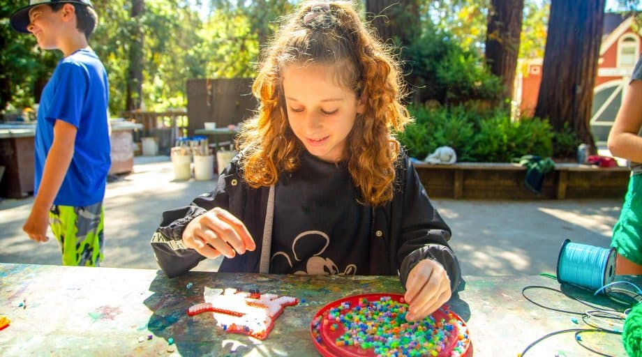 Girl makes bead pattern at summer camp