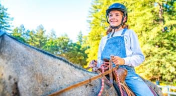 A girl on a horse in overalls