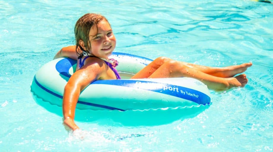 A girl in a donut tube floating in a pool