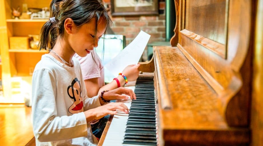 Young girl plays piano at summer camp