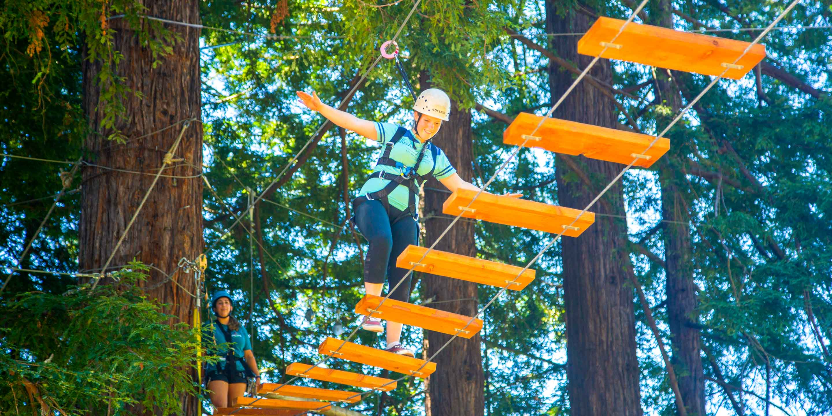 Camper does plank walk on ropes course