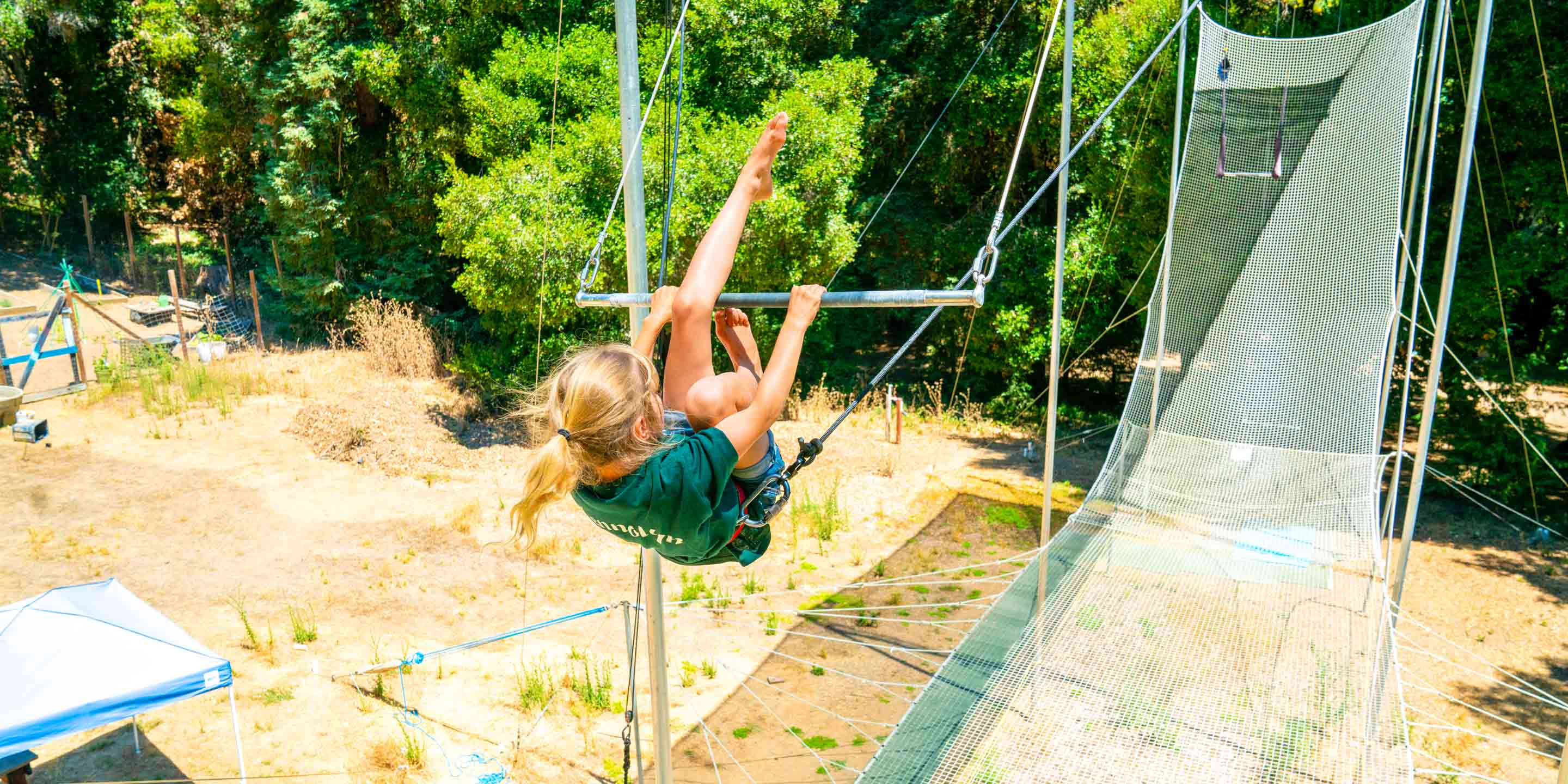 Girl swings legs over trapeze while swinging