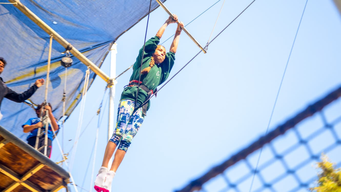 Girl swings on trapeze at summer camp