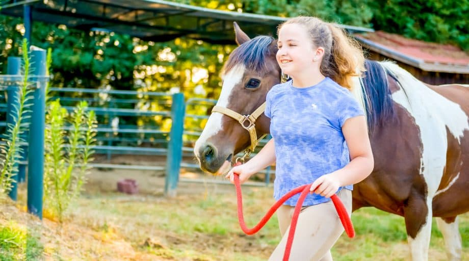 Girl walks horse at summer camp