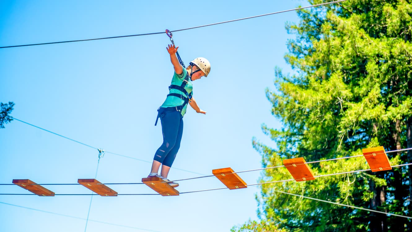 Girl walks across planks of ropes course