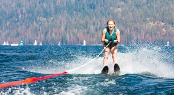 A girl waterskiing and laughing on the lake