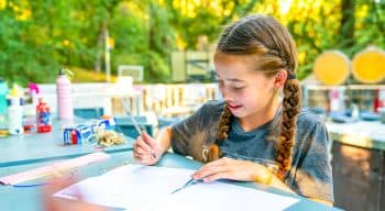 A girl with braids writing a letter