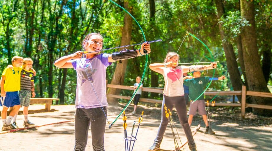 Girls do archery at summer camp