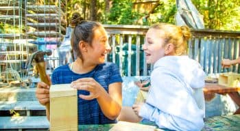 Two girls laughing and talking while building bird houses