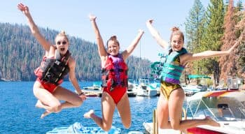 Three girls jumping in the air at the lake with life vests on